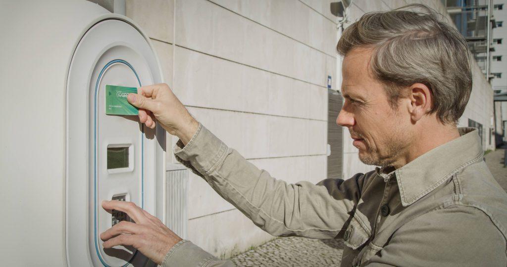 tipos de carregadores de carros elétricos - homem a utilizar posto de carregamento elétrico com cartão
