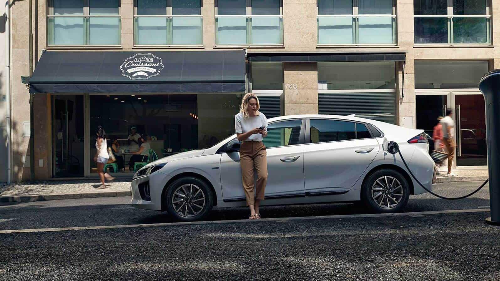 Mulher a carregar o seu carro elétrico na rua