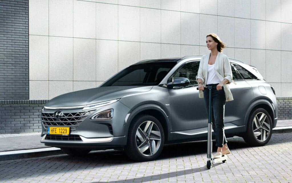 Mulher em trotinete junto a Hyundai Kauai Electric