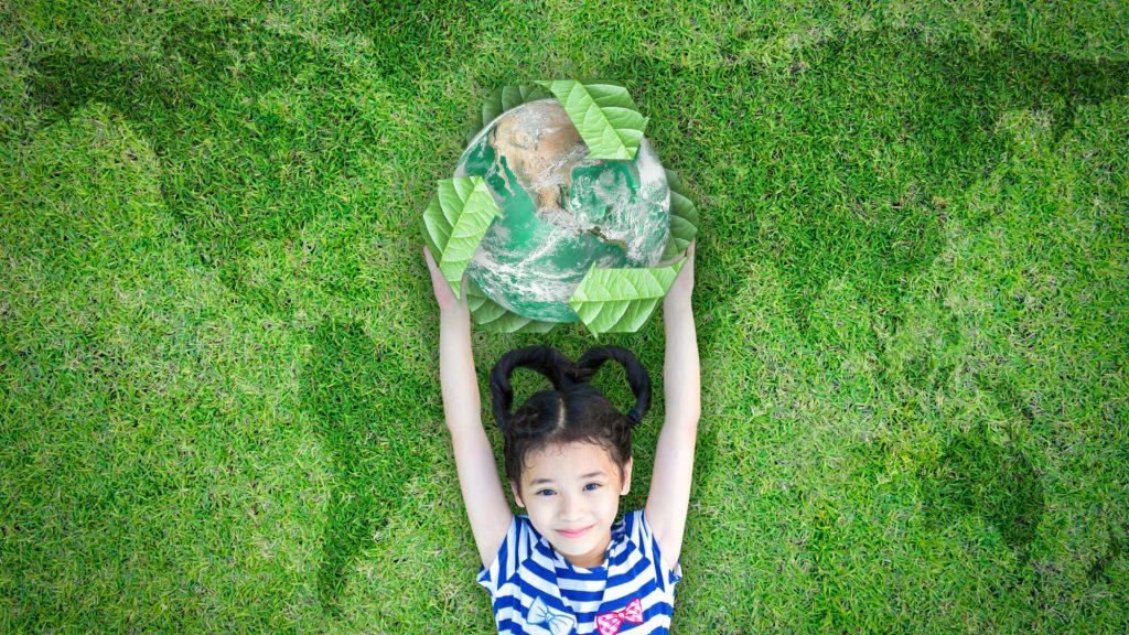 Menina deitada na relva a segurar um símbolo ecológico