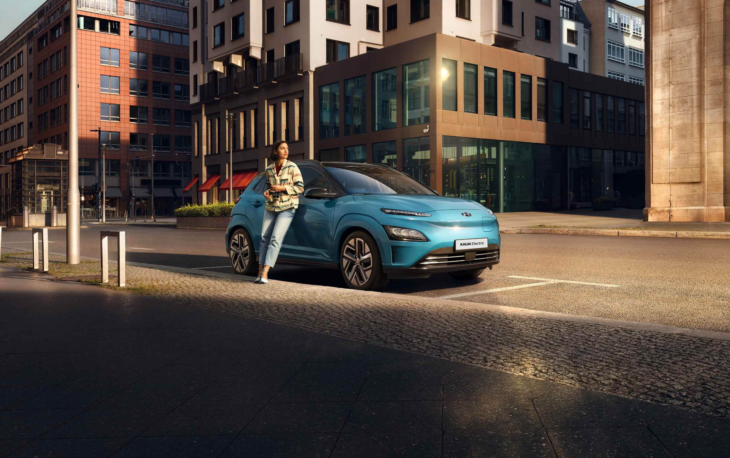 Hyundai Kauai elétrico azul na estrada com pessoa ao lado