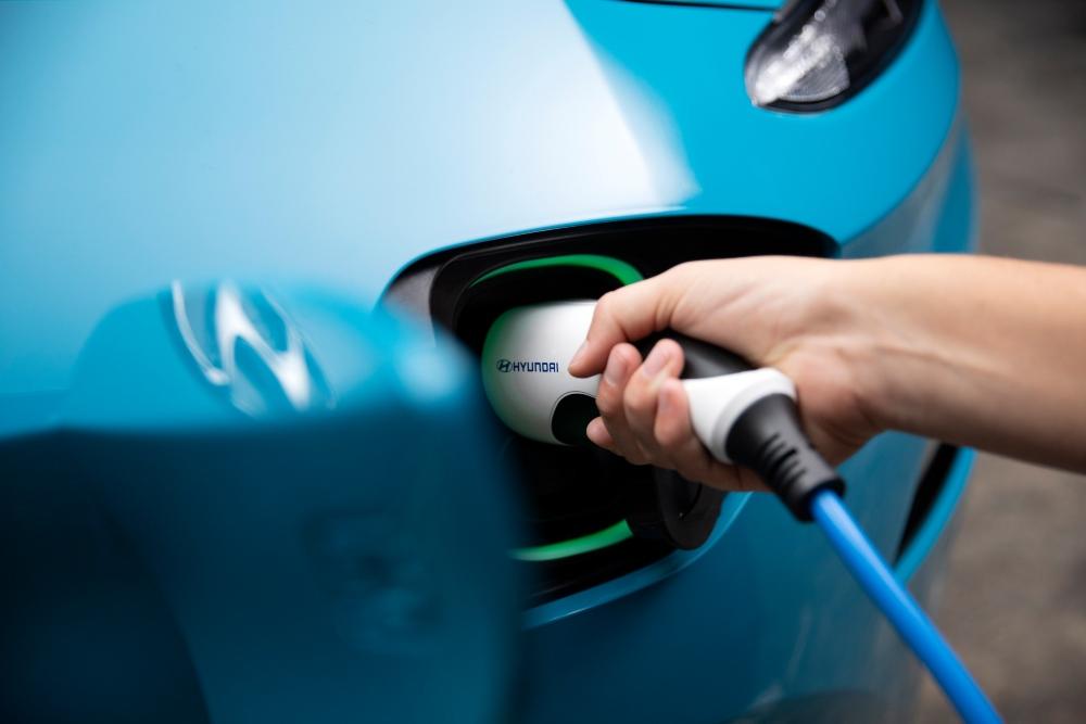 Pessoa a carregar um carro elétrico